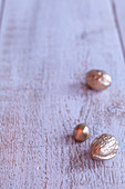 Gold walnuts and acorn on wooden surface