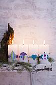 Vier Stumpenkerzen weihnachtlich dekoriert mit verschiedenen Banderolen