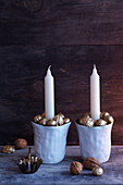 China cups filled with gold-painted nuts used as festive candlesticks