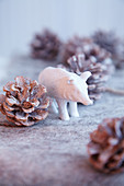 White wild boar figurine amongst pine cones on felt surface