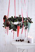 Suspended ivy wreath festively decorated with paper cones and candy canes
