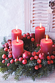 Advent wreath made from red crab apples and red pillar candles