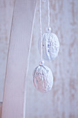 White-painted walnuts decorated with pearls and hung up as Christmas decorations