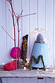 Creative wintry arrangement of natural materials, fairy lights and zinc bucket