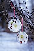 Selbstgemachte Eis-Anhänger mit eingefrorenen Christrosenblüten und Beeren
