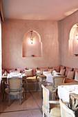 Oriental restaurant in shades of soft pink with lanterns in niches
