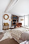Bett mit Tagesdecke, klassiker Ledersessel, Stehleuchten und Schrank im Schlafzimer