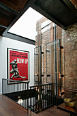 Glass panels covering copper pipes and film poster in stairwell