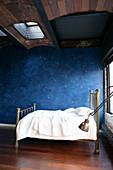 Kinderbett vor blauer Wand mit Sternenmuster unter dem Gewölbe