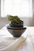 Conifer sprigs in stacked black bowls on table