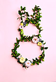 DIY wreaths of leaves with paper flowers in the shape of a rabbit