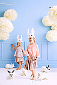 Two girls with DIY rabbit masks and lively bunnies in the room with a light blue wall