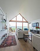 Helle Sitzmöbel und Glasregale in elegantem Wohnzimmer mit Glasfront