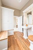 Klassisches Badezimmer in Weiß mit Holzboden