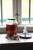 Selbstgemachtes Johanniskrautöl zur Wundheilung in Glas auf Fensterbank