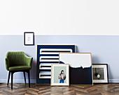 Gerahmte Kunstwerke neben grünem Sessel
