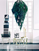 Pine tree hanging upside down over coffee table with candles and chair with gift boxes