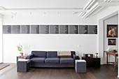Grey sofa below black panels covered with list of painter's names on wall of lounge