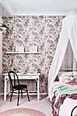 Weisser Schreibtisch mit schwarzem Stuhl und Kinderbett mit Baldachin im Mädchenzimmer mit Blumentapete