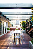 Modern garden furniture on the covered terrace with wooden deck