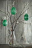Green-painted Easter eggs hung from pussy willow branches in bottle