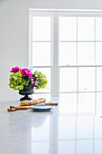 Bread and flower arrangement on worksurface in front of window