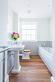 Vintage-style sink against wall tiled to half height with ledge