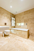 Sand-coloured tiles in spacious bathroom
