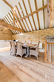 Dining area below exposed roof structure in converted barn