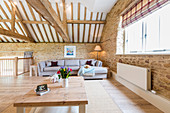 Living area below exposed roof structure in converted barn