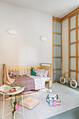 Bed and balance bike in child's bedroom in pastel shades
