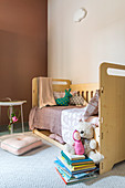 Child's bed in simple child's bedroom in natural shades