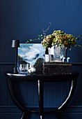 Table lamp, painting, vintage metal box and champagne bucket with flowers on console table