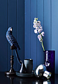 Decorative bird, crockery and glass vase with flower against blue wall