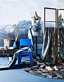Vintage suitcase, blue chair, mannequin and screen with decorative fabric