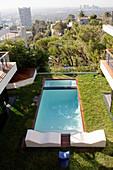 Blick auf einen Innenhofgarten mit Pool und Stadtpanorama