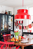 Christmas decorations on round table below red lampshade