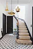 Pendant lamps with golden lampshades in stairwell with cement floor tiles