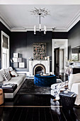 Light sofa set, blue upholstered table and fireplace in the living room with dark gray walls and black floorboards