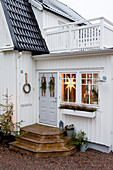 White, Swedish house with Christmas decorations around front door