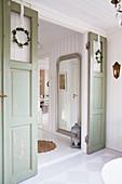 Open, green double doors with Christmas decorations in Scandinavian house