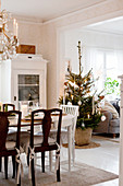 Festively decorated dining table, glass-fronted cabinet and decorated Christmas tree in Scandinavian dining room