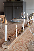 Handmade Christmas decoration made from natural materials and candles on dining table