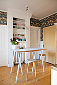 High table and bar stools in front of shelves of crockery in kitchen with wooden floor