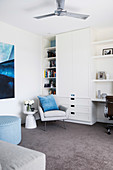 White wall unit with integrated desk, armchair and side table in front