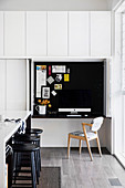 Kitchen counter with black bar stools, mini home office behind folding sliding element