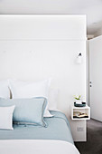 Double bed with white and light blue bed linen in front of the room divider in the bedroom