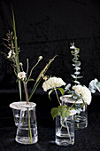 Flower arrangements in vases with perforated lids made from modelling clay