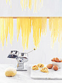 Home-made pasta with a pasta maker, pasta dough and eggs