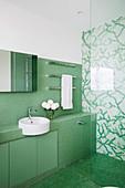 Blick ins Badezimmer mit grünen und grün-weißen Mosaikfliesen